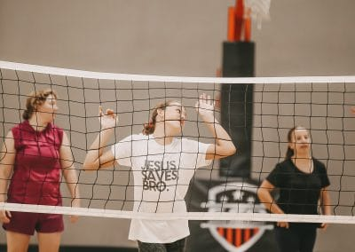 Girl with her hands on the volleyball net.